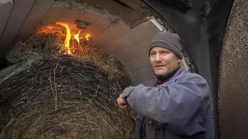 Lars Otto Grundt fyrer med halm og tømmer